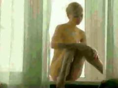golden-haired young hottie undress in window